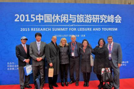 8 people standing in front of curtain with English and Chinese text reading 2015 Research Summit for Leisure and Tourism